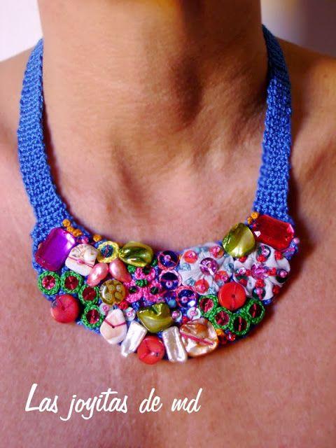 Collar babero de croché en color azul.  Cosido a mano sobre él: yoyos de tela bordados, lentejuelas de colores, nácar, coral, cristal de murano, cristal de swarovski y rosetas.