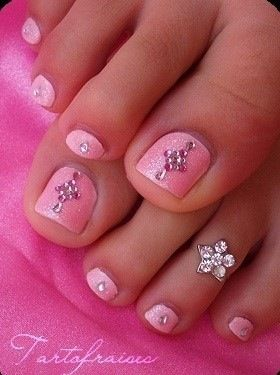 Pretty pink toe nails with diamond embellishments.