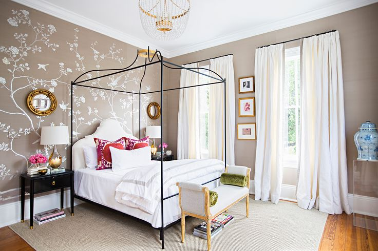 illuminated by a clear beaded chandelier this stylish bedroom boasts a a black canopy bed accented with gold and dressed in gray board hotel bedding topped