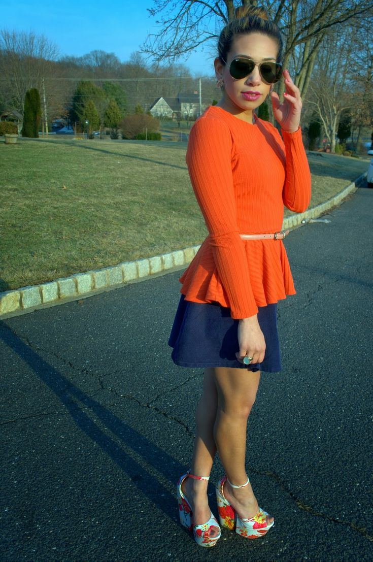 Bayann from Bay's Style diary wearing a navy blue skirt and an orange peplum top and floral platform sandals