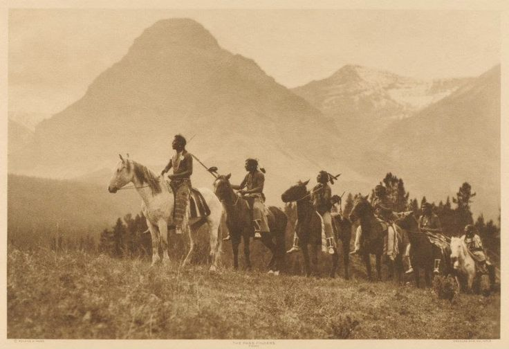 This is a rare 1908 natural photo of Blackfoot Indian warriors on horseback.