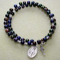 """A rosary is a prayer tool that helps us to meditate on the life of Jesus Christ while articulating a background """"soundtrack"""" of Our Fathers and Hail Maries. Rosaries are made in different ways; one of my favorite is the coil memory wire wrap rosary bracelet. The coil memory wire wrap rosary bracelet is a fun project to make on your own or..."""