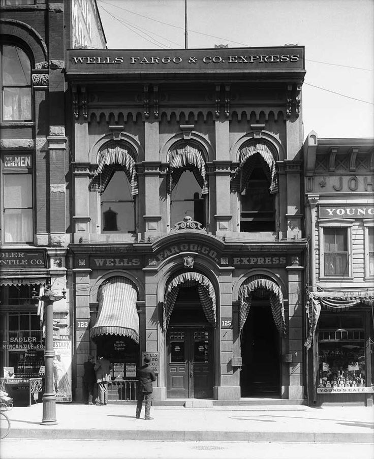 """Wells Fargo and Company building, April 4, 1912. Wells Fargo erected this stone building at 125 South Main in 1866. It was one of three similar buildings with tall arched windows that stood on the east side of Main Street between 100 and 200 South streets. Shipler simply labeled this image """"Herald-Republican new building site."""" Although the Herald-Republican newspaper never followed through on its plans, the building was soon demolished and a new bank was erected in its place in 1913."""