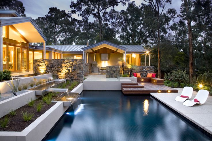 View across the pool to the outdoor kitchen and entertaining area at Eltham residence in Australia by TLC Pools & Landscapes