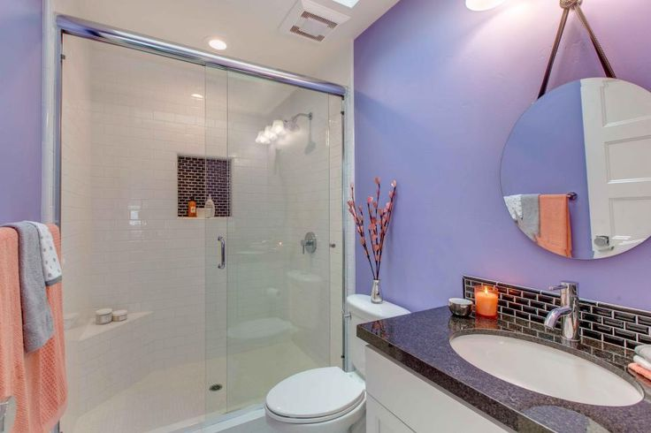 Lavender is a whimsical choice for this small bathroom, accented by pops of brown and melon orange. A walk-in shower with a sliding glass door both saves space and adds a welcome luxe touch.