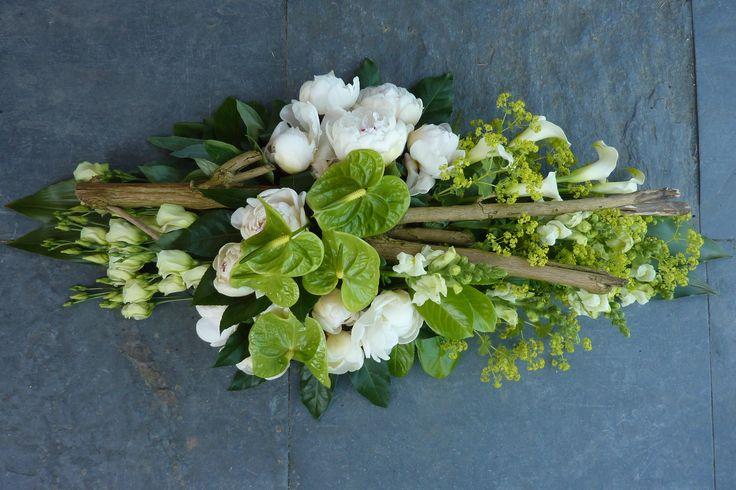 Een wit/groen kleurig rouwstuk, gestoken op oasis met stronk. Langwerpig, verwerkt op groepen. -Prijs: €125