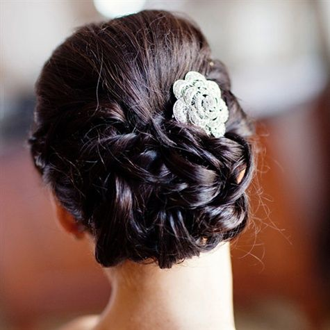 For a sophisticated look the bride wore her hair up and pinned into a low hair bun which she accented with a brooch made of crystals and rhinestones.