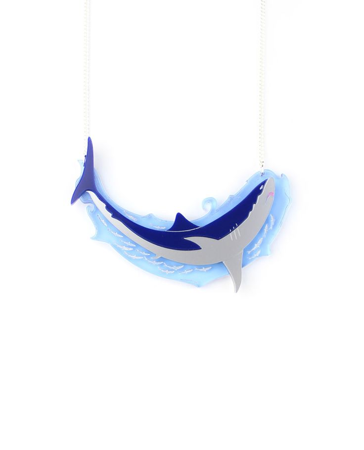 Shark necklace, A big white shark swims in the deep ocean waters chasing its prey with a mouth full of sharp tusks. Its speed makes it one of the most feared creatures in the ocean.  Laser-cut etched fluorescent blue acrylic water with details painted by hand and blue and silver shark. Made and assembled by hand.  LIMITED EDITION to 15 pieces.
