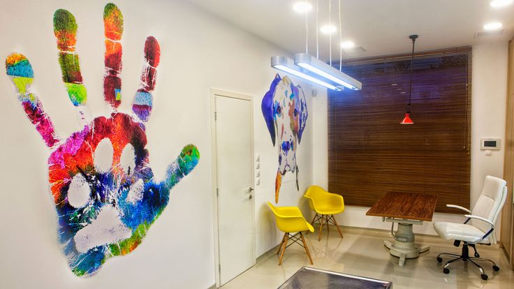 Graphic design applications with vivid colors and contemporary pieces of art on the walls of the examination room communicate the relationship between humans and animals