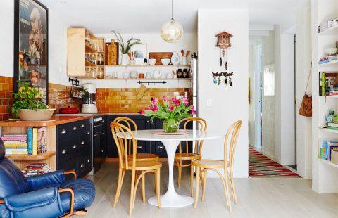 Esta cozinha possui as prateleiras abertas, plantas e cadeiras Thonet -- uma graça