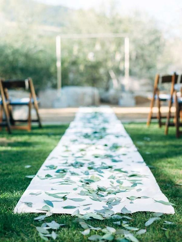 white aisle runner decorated with scattered eucalyptus leaves