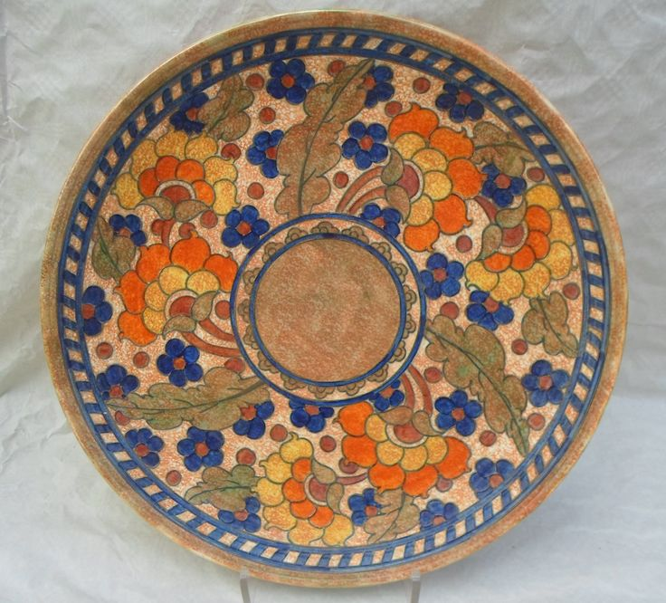 A large 1930s Crown Ducal wall plaque, designed by Charlotte Rhead in the 2681 Byzantine pattern, having a tube-lined decoration of stylized flowers and leaves on a mottled ground, printed and tubed marks verso to include a Rhead facsimile signature, 44cm diameter