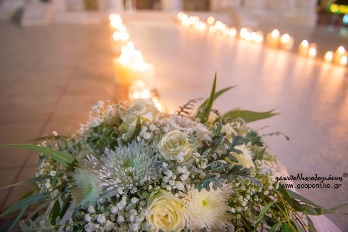 στολισμός διαδρόμου με επιδαπέδια ανθοδέσμη και διάδρομο από λευκό χαλί που πλαισιώνεται με κεριά. church decoration wedding