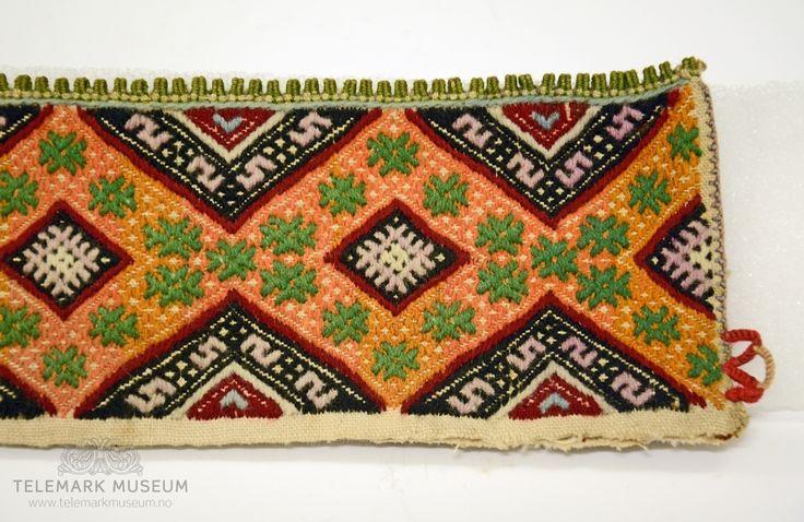Fra protokollen:  Kvarde av bomuldstøi, sydd i kulørt smöigsaum. Mønster: en gul bord av rhomber, hvori grønne #, med halvborder i sort med (liggende) S'er paa hver side. Grønne tagger.   Halskvarde til kvinneskjorte fra Øst-Telemark.