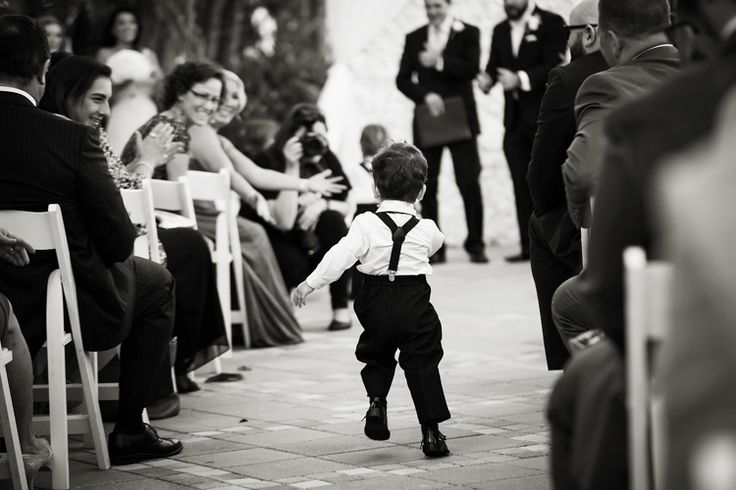 Adorable wedding photo idea of the ring bearer running down the aisle. Too cute! (Limelight Photography)