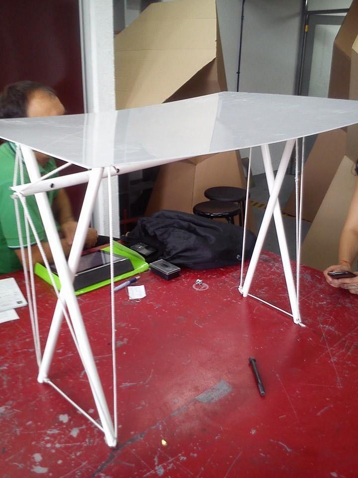 mesa de escritorio con tubos de aluminio y cuerdas sujetadas con tensión