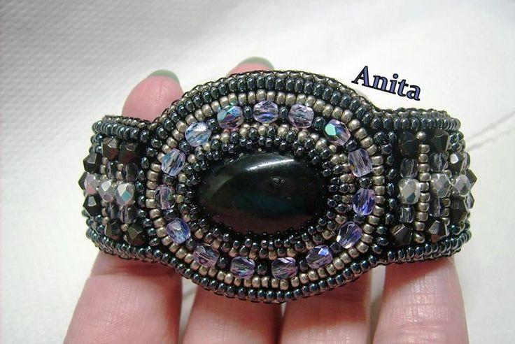 K-701. Fekete színű, Achát köves, szürke, lila és ezüst színű, üveg gyöngyös, gyöngy-hímzett, gombbal kapcsolható karkötő. A karkötő hátulja műbőr. A kapcsolója fém gomb. A karkötő mérete: 19 cm. 3700.-Ft