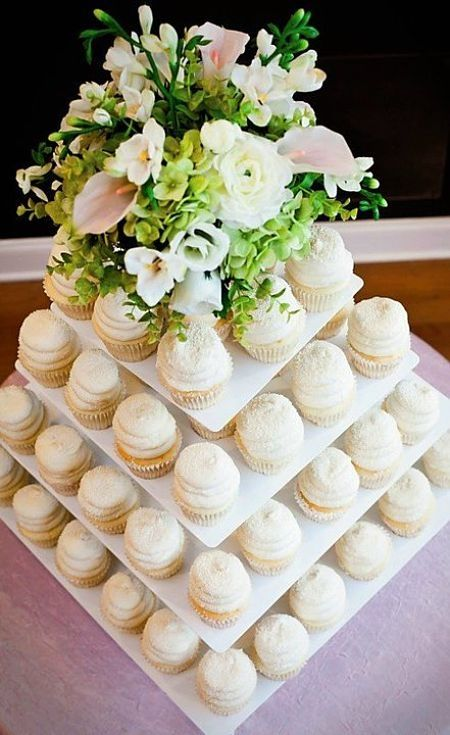 This cupcake display stood out the most out of most cupcake tiers I've seen because 1. They used a center piece rather than a giant cupcake or a cake itself. 2. The tier are glass square plates instead of round. It definitely makes simple cupcakes stand out a whole lot more than it is. Love this setting