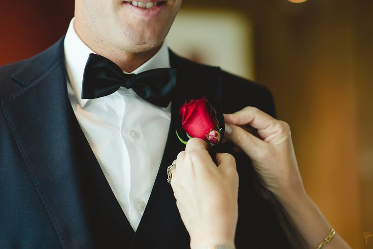 Red rose button hole on navy suit with bow tie.