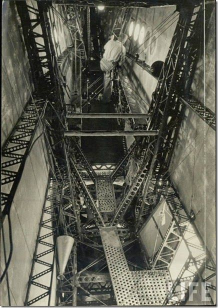 The interior of the Hindenburg's lower tail fin. The starboard access hatch can be seen at lower right, and the control area for the aft landing wheel can be seen between the pair of V-shaped girder arrangements at lower center. Further forward from this position, a trio of portholes in the starboard side of the fin mark the location of the emergency helm control stand. The man in the photo is standing at roughly the same spot as the Chief Engineer's landing station.