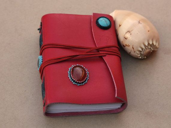 """A blank journal bound in brilliant red leather, """"Inverted"""" plays with colour and line to catch the eye. Turquoise, Carnelian and Hematite cabochons are adorned with delica seed beads, emphasizing the striking combination of red and blue which are located opposite each other on the colour wheel."""