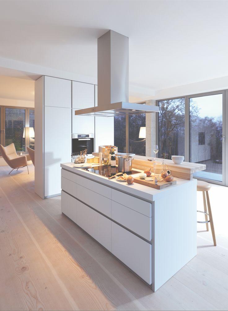 bulthaup - b1 keuken - de keuken in deze loft draagt transparantie hoog in het vaandel. Het laminaat werkblad van het keukeneiland is puristisch wit en wordt gecombineerd met een barblad uit massief ahornhout. De aansluiting van achterwand en zijkanten is in verstektechniek uitgevoerd, zodat het keukeneiland als een beeldhouwwerk in de ruimte staat
