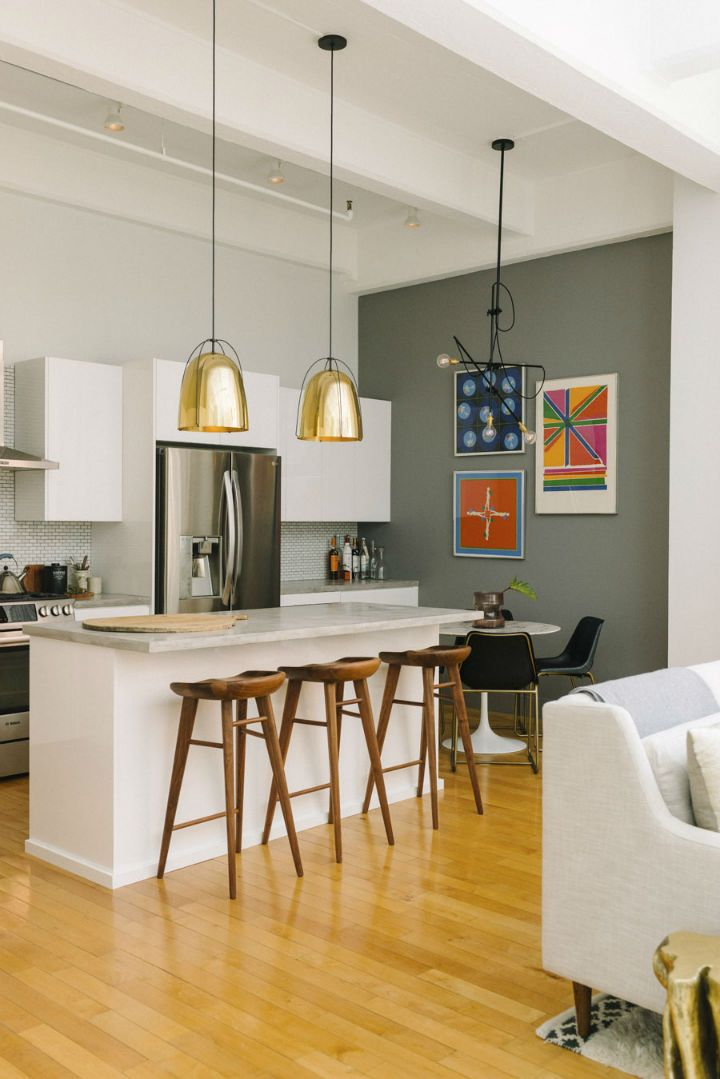 Amazing kitchen design idea with large kitchen island, colorful framed pictures and brass pendant  lights