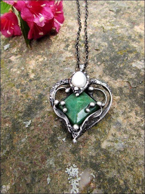"""Náhrdelník+-+el+corazón+Náhrdelník+-+,,el+corazón""""+je+vyroben+pomocí+cínu+s+příměsí+stříbra+(+cín+neobsahuje+olovo),+na+náhrdelník+jsem+použila+exklusivní+broušený+kámen+z+přírodního+(ale+dobarvovaného)+smaragdu(původ+Brazílie),+drátek+a+bílou+perlu+říční.+Přívěsek+je+patinován+a+následně+očištěn+specielním+olejem.+Velikost+šperku+je+6,5x3,5cm.+Je..."""