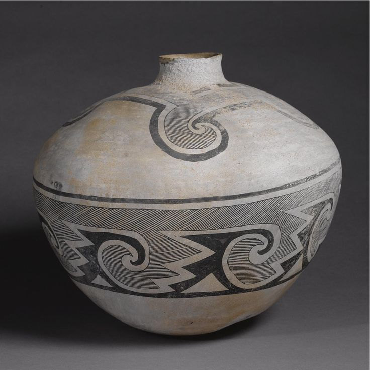 """A Large Socorro Black-On-White Storage Jar circa 1200 A.D., with small base, flaring sides and exaggeratedshoulder, painted with a broad friezeof scrolling elements against a finely hatched ground, the small cylindrical neck enclosed with a stylized """"collar"""" of similar elements. height 15 1/2 in. by diameter 17 in. Sotheby's. AMERICAN INDIAN ART 18 May 2007. NY."""