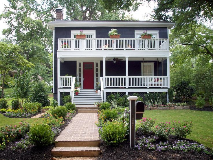 A red front door adds a splash of color to this charming Cape Cod with a second-story porch. Major curb appeal points are awarded for the neatly landscaped mailbox and window boxes.