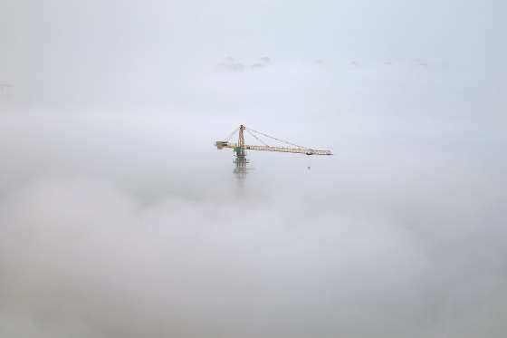 A crane is seen among thick fog in Yantai, Shandong province, China, October 19, 2016. China Daily/v... - REUTERS