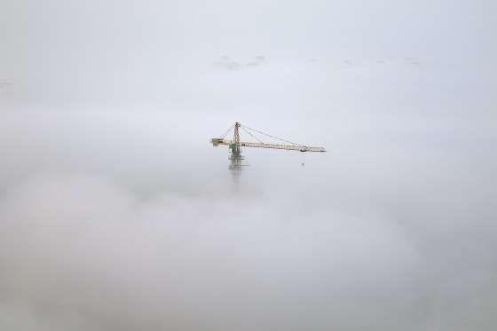 A crane is seen among thick fog in Yantai, Shandong province, China, October 19, 2016. China Daily/v... - REUTERS