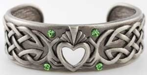 Rich in poetic meaning, this bracelet proudly displays the Claddagh at its center. This symbol, consisting of two hands grasping a heart, is said to be born of rich Irish tradition of offering your heart and love to another. This is expanded upon, with the hands sweeping back into an elaborate design of celtic knots along the bracelet's band, helping to create a symbol of unity, love and eternity. Accented by numerous green and blue faceted gems,