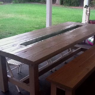 Distressed picnic table with beverage trough in center . One on today's homeowner show redid an old picnic table