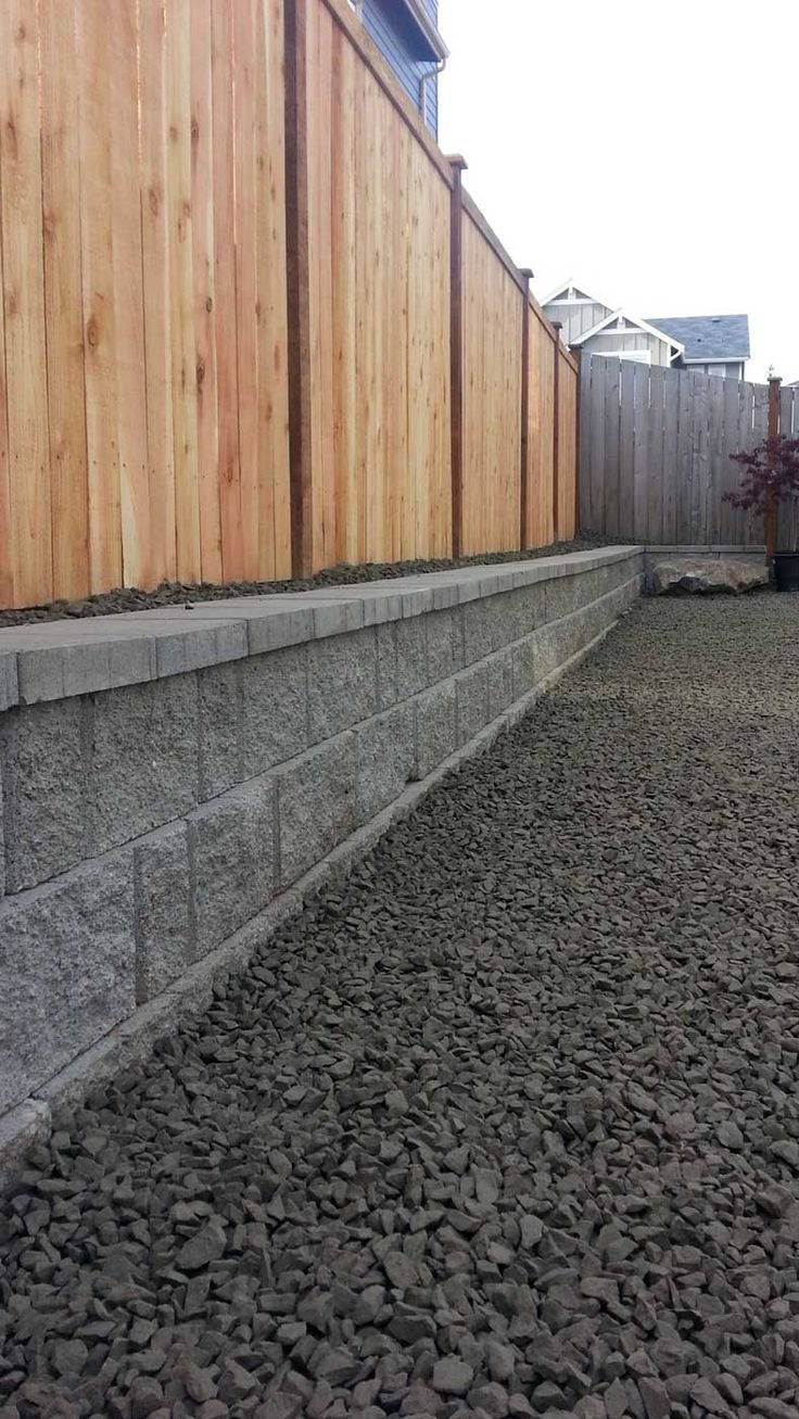The rear of the property now has a 2 foot high retaining wall, which allowed us to regrade the backyard to a clean, flat surface. By adding the cedar fence on top of the retaining wall, we were able to effectively build a 7 foot barrier on the rear of the property, adding even more privacy.
