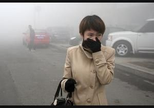 A woman covers her mouth while walking through heavy smog in Harbin, China, in the northern section of the country. The smog level is forty times higher than the the level considered safe by the World Health Organization, and caused school and highway closures in the region.