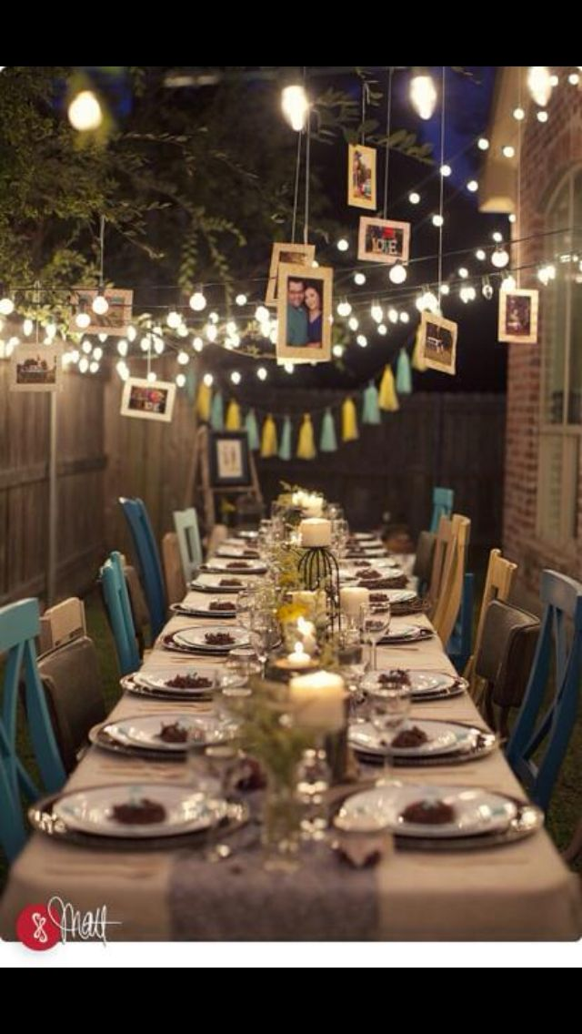 This is a beautiful 10 year wedding anniversary party idea! I love the white lights and the pictures hanging from the trees and the multiple colors of teal chairs. ❤️