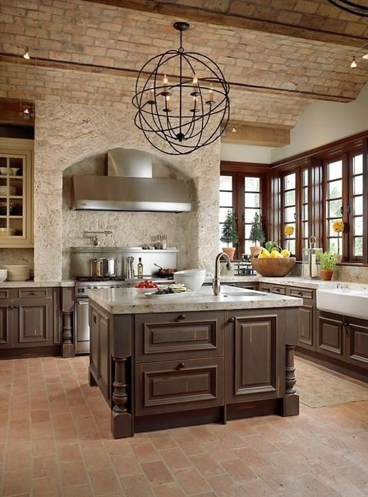 Love this kitchen. Dark cabinets, light counters, brick, stone, great metal light fixture