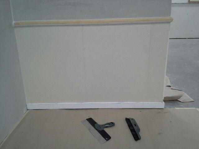 Grundpapir sat op på bås under vægliste.