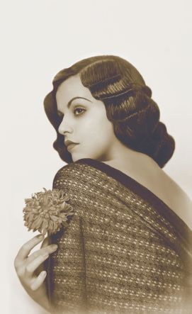 1920's Finger Waves    This beautiful woman has finger (crimped) waves that look like organized rows on long brunette locks that cascade over one shoulder.