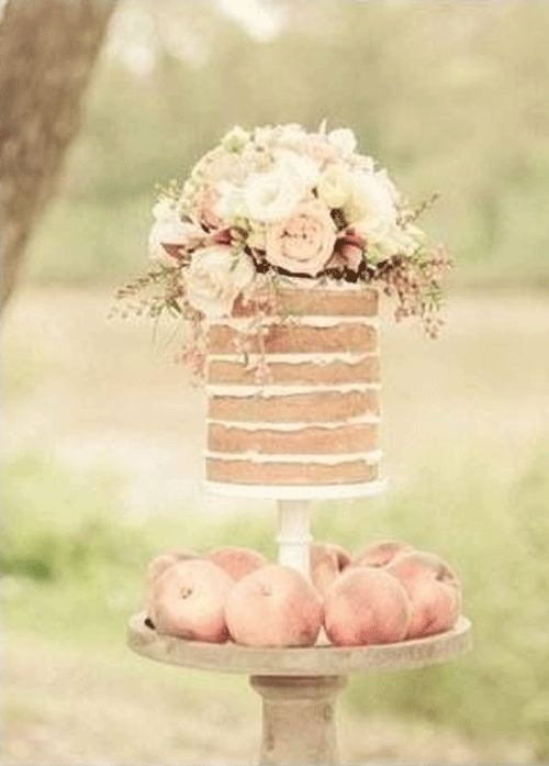 Flower-topped naked cake surrounded by pieces of fruit #wedding #trends #cakes