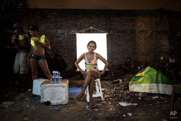 """In this March 18, 2015, photo, Carla Cristina, 26, poses for a portrait next to her water stand in an open-air crack cocaine market, known as a """"cracolandia"""" or crackland, where users can buy crack, and smoke it in plain sight, day or night, in Rio de Janeiro, Brazil. Carla Cristina sells cups of water with an aluminum seal, which users will transform into makeshift pipes for smoking their crack. (AP Photo/Felipe Dana)"""