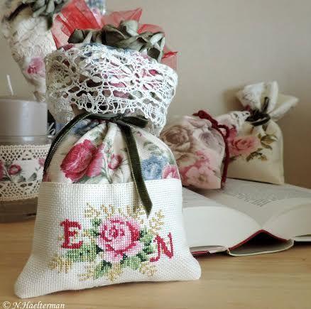 Zakje in gebloemde stof,met een roos en initialen in kruissteek, afgewerkt met een kantenboord, organza en roosjes....
