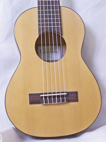 """""""Introducing the new groundbreaking Guilele from Cordoba Guitars! A small guitar with a ukulele sound, feel and size. Considered to be a true travel guitar, this small six string is light, portable and a great way for guitar players to segue into the ukulele world. The Cordoba Guilele is tuned up a 4th (same as a guitar with a capo at the 5th fret - A D G C E A - low to high)and is built with a solid spruce top, mahogany back and sides, a rosewood fingerboard, and a natural satin finish."""""""
