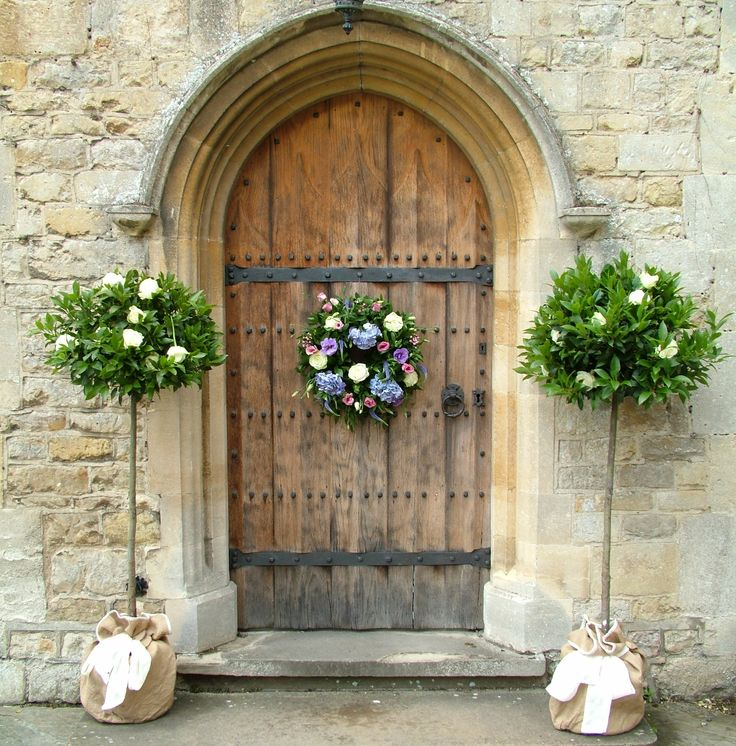 Bay trees and a flower filled wreath on the front door of Notley Abbey