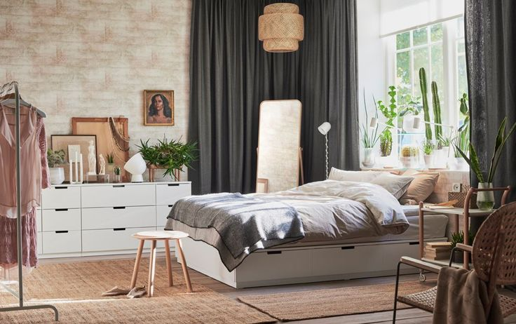 White bed with drawers in a large bedroom with exposed brick, gray curtains and jute rugs.