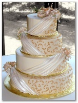 Buttercream iced with Pearlized Fondant Drapes, Gold icing scrolls and Gumpaste Flowers