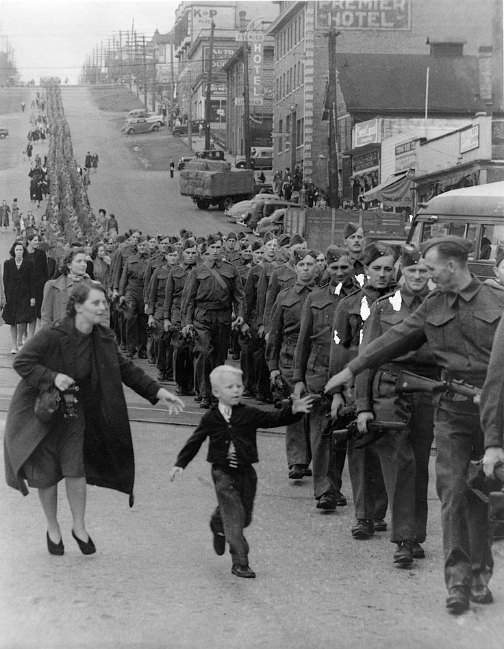 "Claude P. Dettloff    ""Wait For Me Daddy"", October 1, 1940: A line of soldiers march in British Columbia on their way to a waiting train as five-year-old Whitey Bernard tugs away from his mother's hand to reach out for his father."