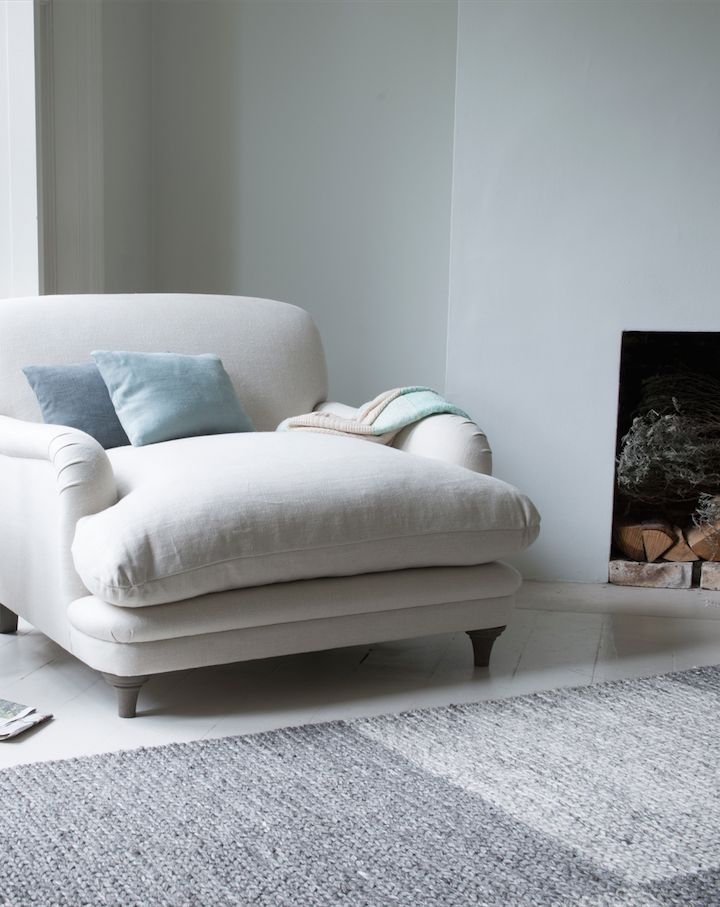 Loaf's Pudding armchair in cream linen sat by the fireplace