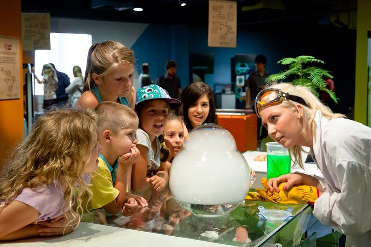 A group of young children are looking at a clear glass bowl with an opening at the top and foam bubbles coming up through the opening. A young woman is also looking on wearing a lab coat and gloves.